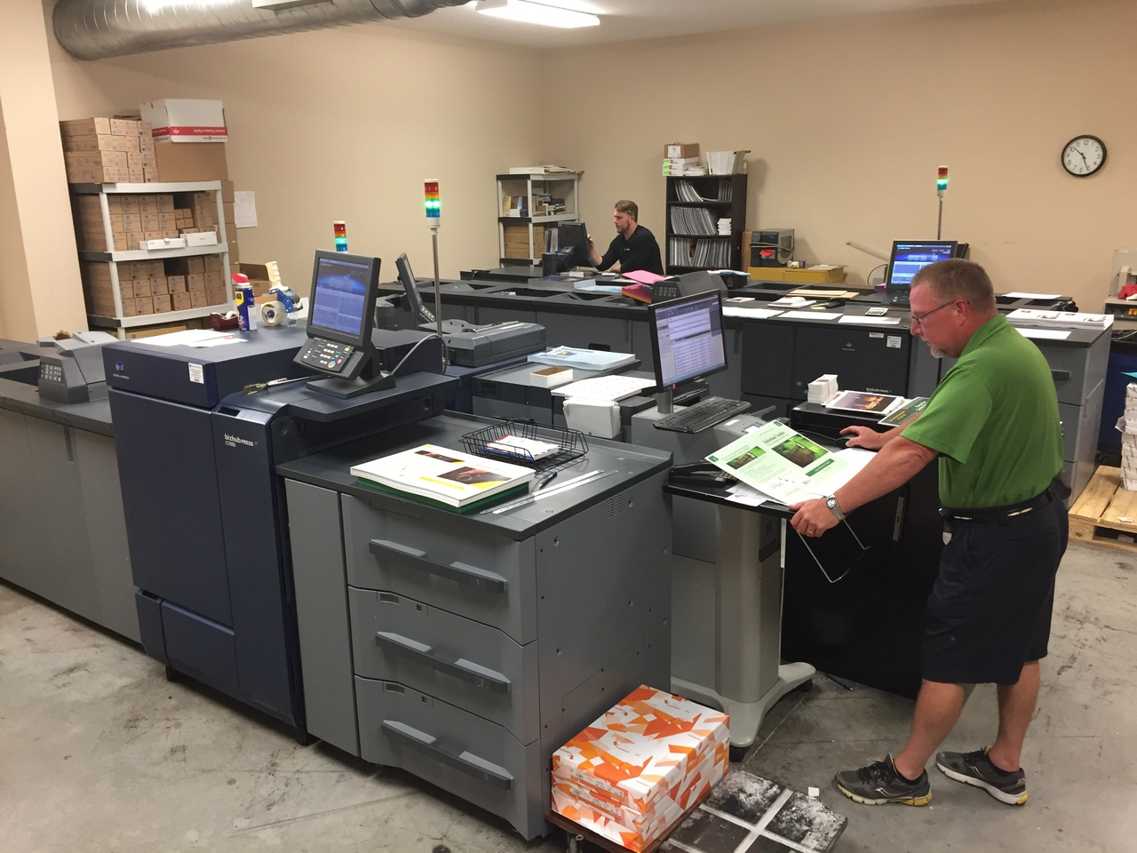 A photo of the local printshop owner, checking up on a book cover.