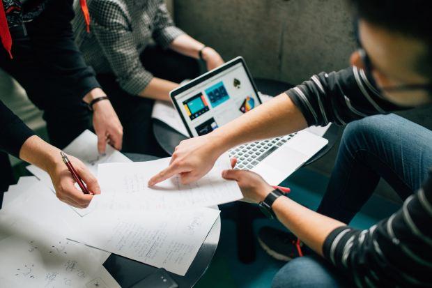 teamwork over computer & paper