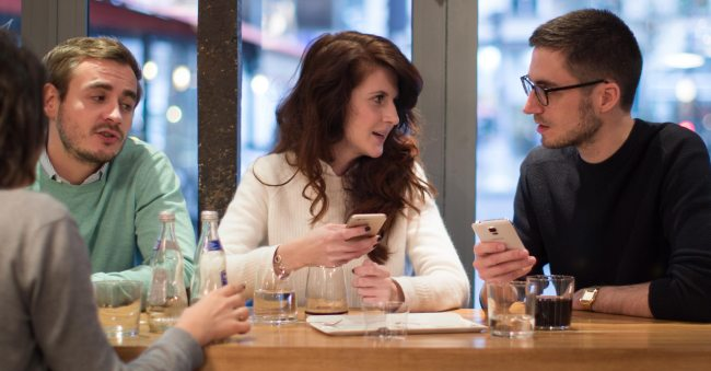 Millennial adults sitting around a table having a lively discussion and sharing stories.