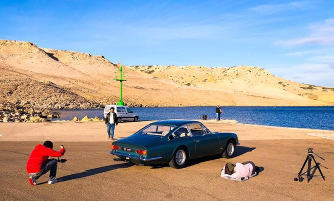 A photographer taking photographs of a classic car.