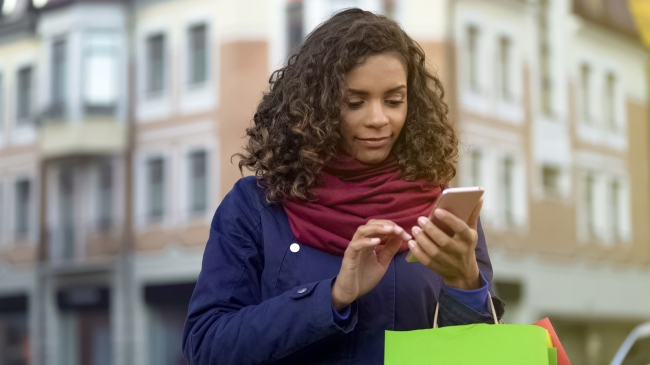 Woman looking shopping on her mobile phone, carrying a few shopping bags. Strong Customer Authentication (SCA) will require a second form of authenticating online purchases.
