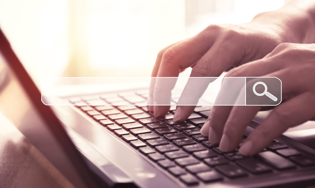 hands using a keyboard with a search bar on top