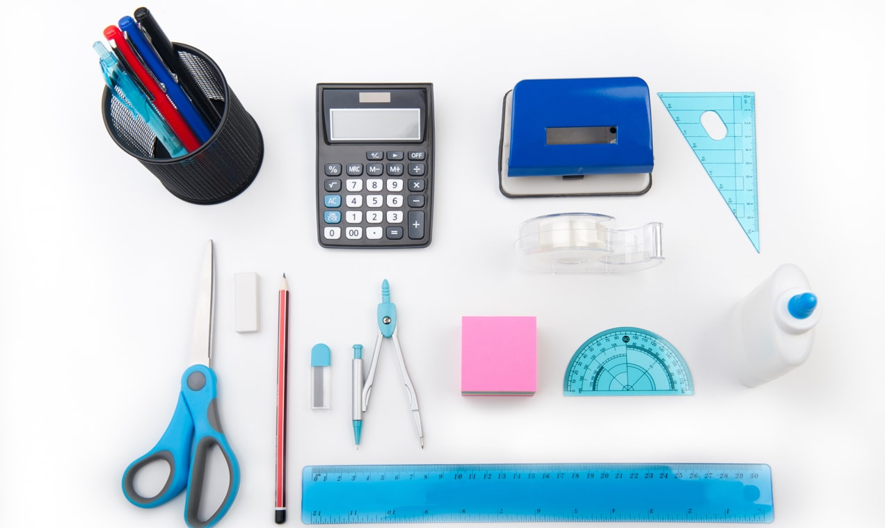 Office products on a table - pens, ruler, sticky notes, and more.
