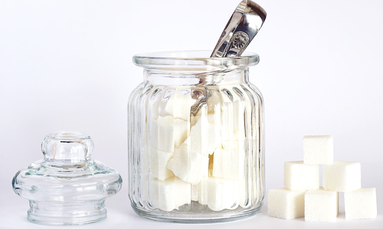 Jar of sugar cubes on a white table.