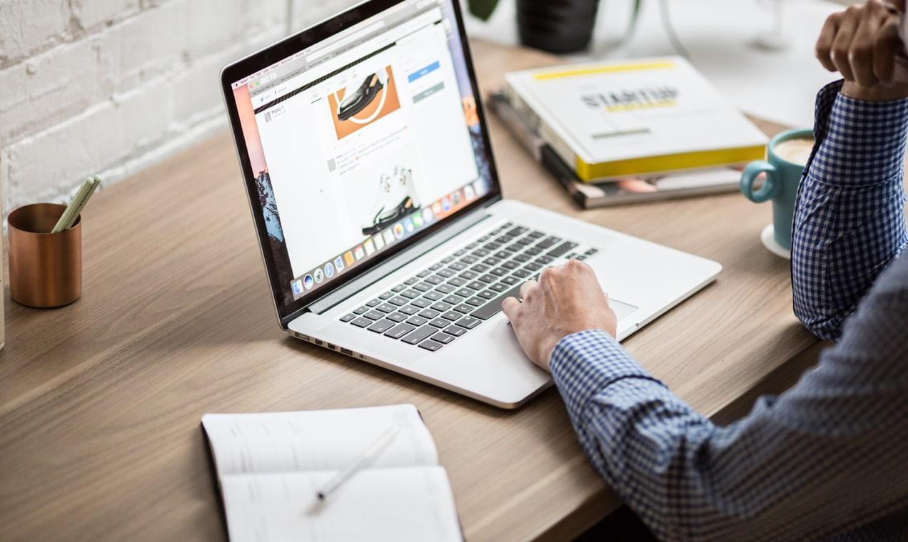 ahşap masa başında bir dizüstü bilgisayar kullanarak adam