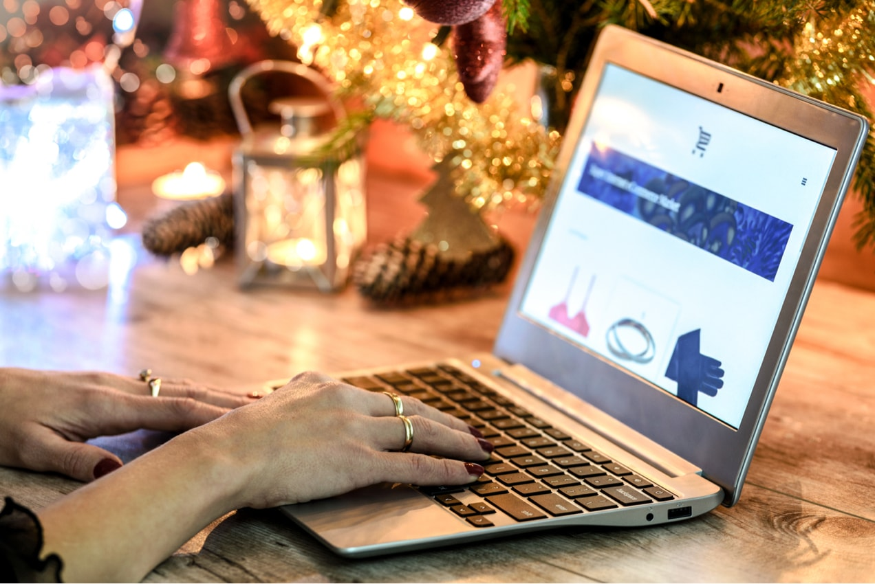 woman holiday shopping on a computer with a Christmas tree in the background