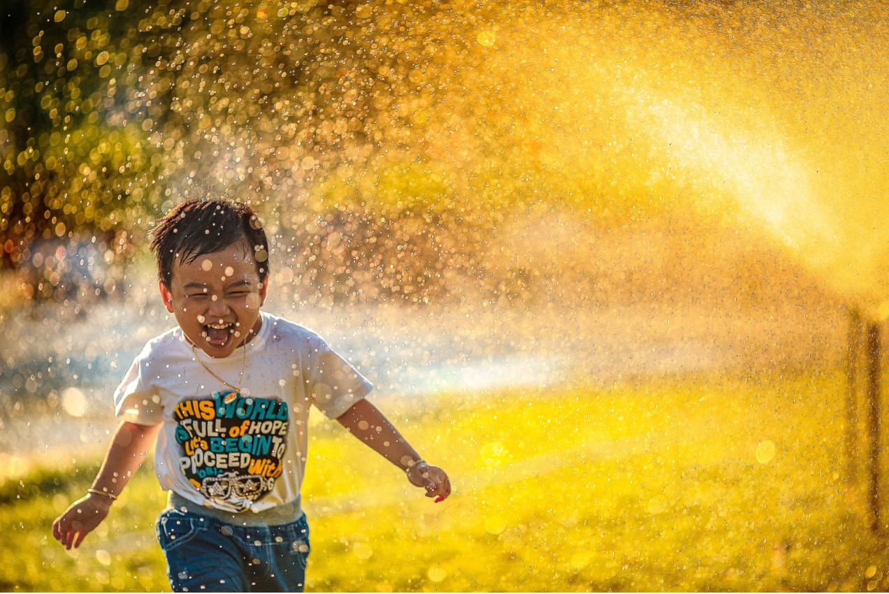 child laughing and running through water, face looking at the camera