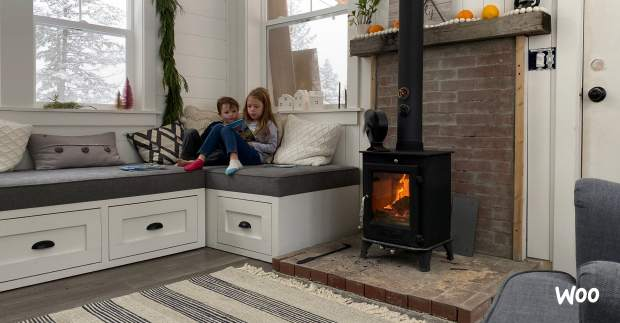 kids reading in front of a tiny wood stove