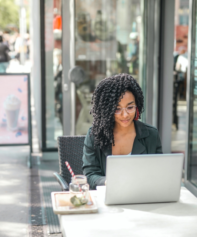 Woman working on a laptop from an outdoor cafe